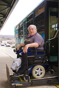 A picture of Bob Dubbs in front of an AMTRAN Bus