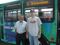 A picture of Justin Hickox and his favorite AMTRAN driver Sam in front of an AMTRAN bus